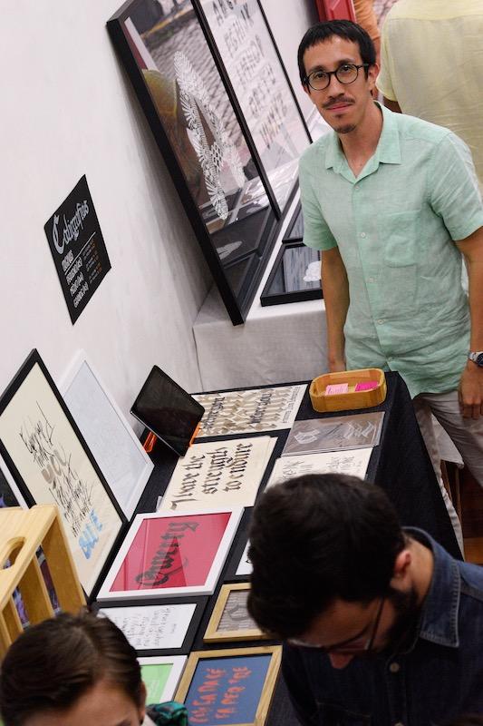 Ivan Jerônimo entre os trabalhos de caligrafia na Feira de Artes de Florianópolis