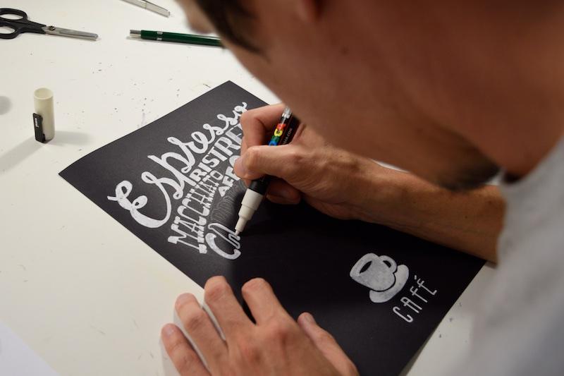 Início do lettering: passando a caneta branca por cima do esboço a lápis